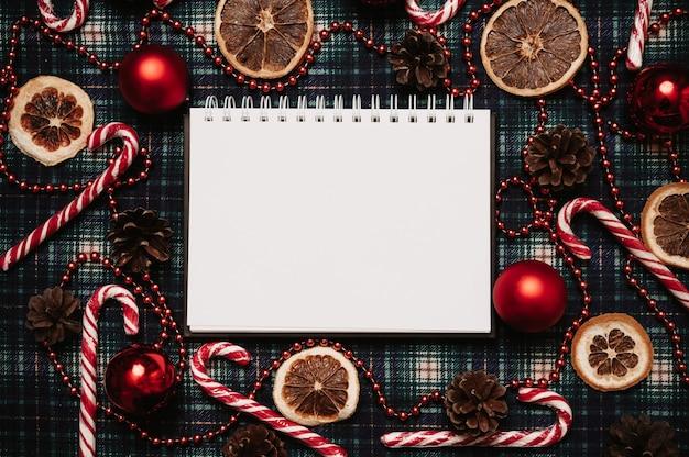 Рождество новый год бумажная рамка, плоский стиль с видом сверху с рождественскими украшениями из шаров, конусов, рождественских тростей на фоне в клетке. место для вашего текста