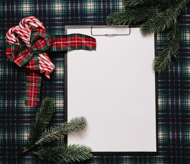 Рождество новый год бумажная рамка, плоский стиль с видом сверху с рождественскими украшениями из рождественских тростников и еловых веток на фоне в клетке. место для вашего текста.