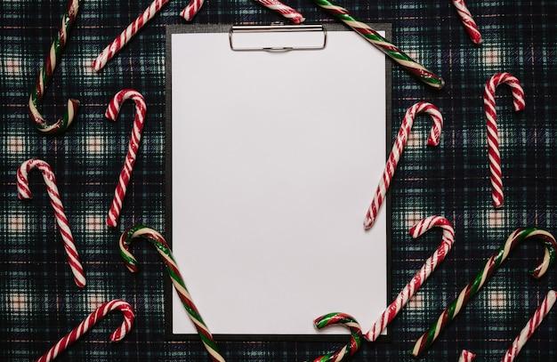 Рождество новый год бумажная рамка, плоский стиль с видом сверху с рождественскими украшениями из рождественских тростей на фоне в клетке. место для вашего текста.