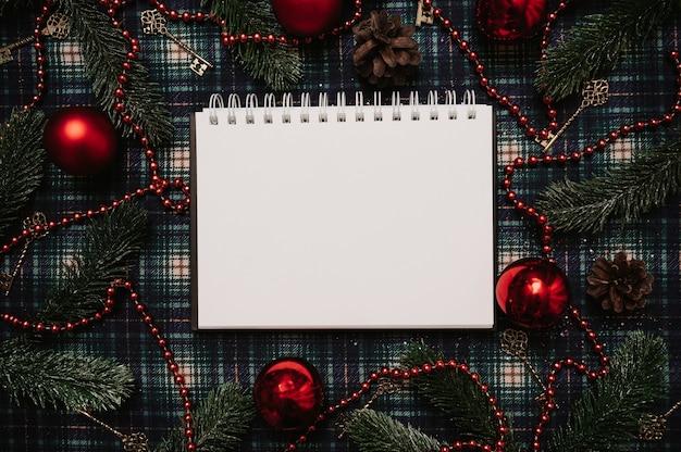 Рождество новый год бумажная рамка в стиле flatley с видом сверху с елочными украшениями из шишек, шаров, еловых веток на фоне в клетке, место для вашего текста