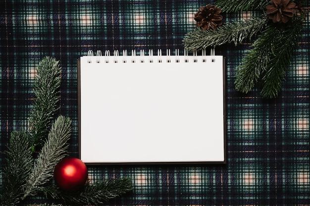 Рождество новый год бумажная рамка, плоский стиль с видом сверху с рождественскими украшениями из шишек, еловых веток на фоне в клетке, место для вашего текста.