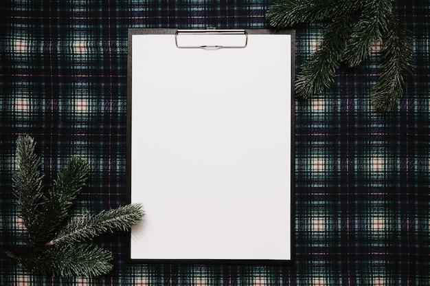 Рождество новый год бумажная рамка в стиле flatley с видом сверху с елочными украшениями из еловых веток на фоне в клетке, место для вашего текста