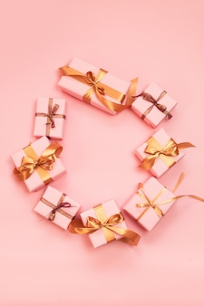 Christmas or new year paper pink gift boxes decorated with shiny gold ribbons on a pink background.