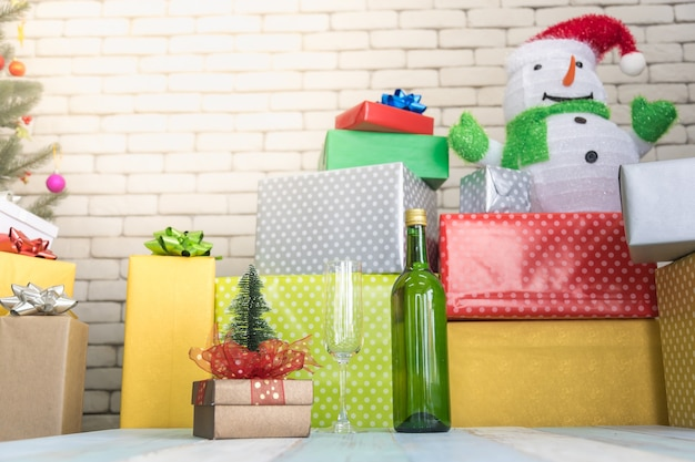 Christmas, new year party concept. closeup of green wine bottle and glass with many colorful gift boxes and doll and xmas tree on wooden table.
