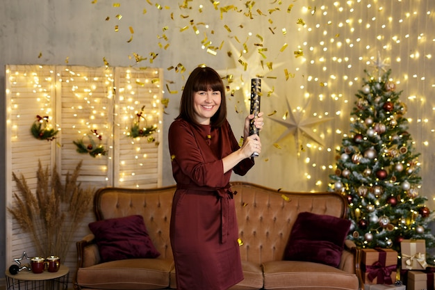 Christmas or new year party - happy young woman with firecracker and golden confetti in decorated living room with christmas tree and garland lights