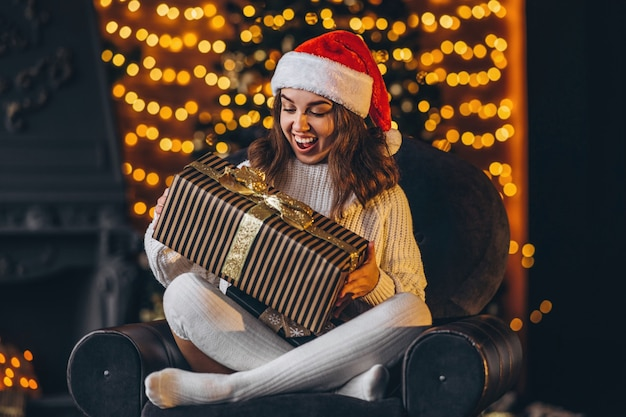 Christmas, new year. pretty woman in warm sweater sitting on the chair at home with gift box