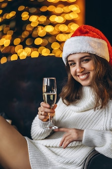 Christmas, new year. pretty woman in warm sweater sitting on the chair with champagne