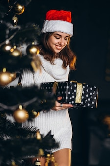 Christmas, new year. pretty woman in warm sweater, socks and christmas hat, decorating new year tree