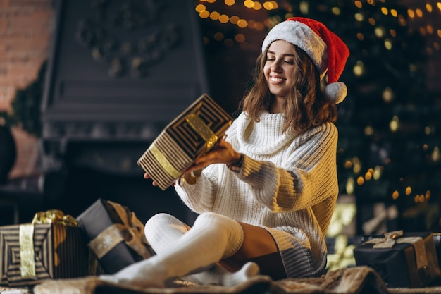 Christmas, new year. pretty woman in warm sweater, socks and christmas hat, sitting on the floor