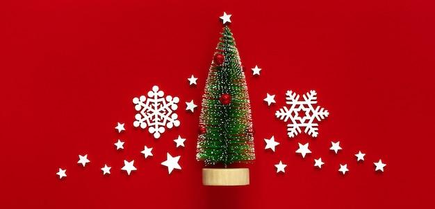 クリスマス、新年の赤いフラットレイ構成。クリスマスの白い装飾、赤い背景の上の装飾的なモミの木。