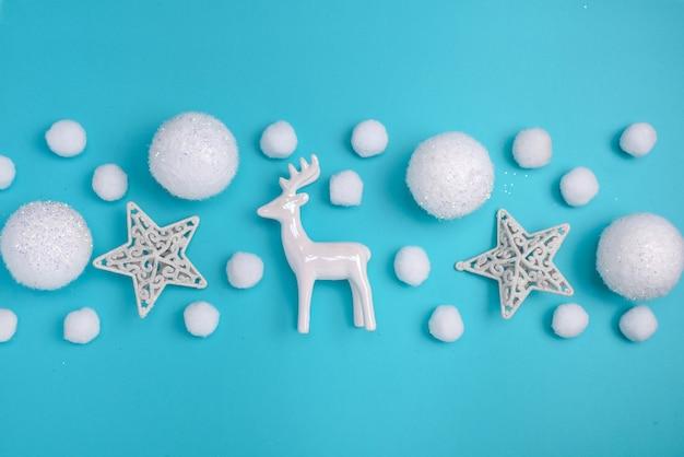 Рождество, новогодняя граница плоской планировки из белых шаров, снега, звезд и оленей. снежный праздничный узор на голубом фоне