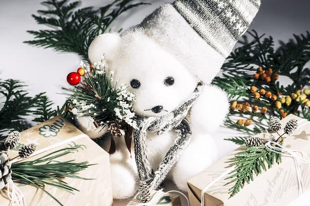 クリスマスの新年の作曲。銀の帽子をかぶったクマとクリスマスの松ぼっくりとボックスギフトは、白い背景の上に横たわっています、