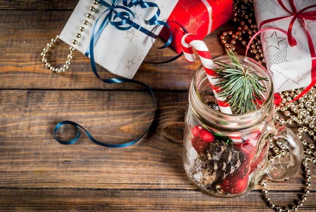 クリスマス、新年のコンセプト。クリスマスの飾り、モミの実、人工雪、キャンディケイン、モミの枝が付いたメイソンジャー。木製のテーブル背景。コピースペース