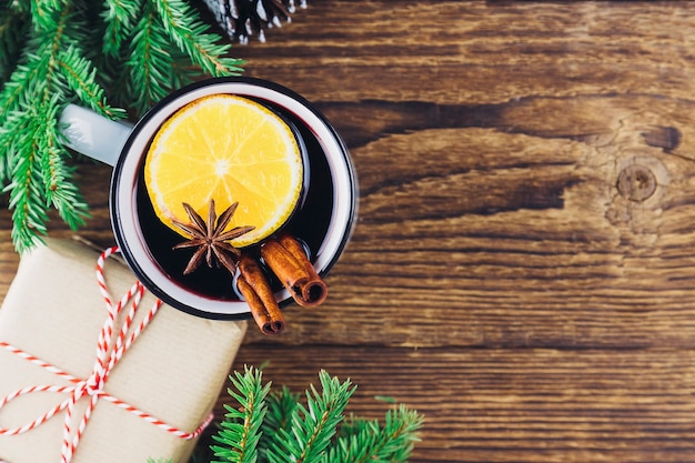 Christmas and new year's drink hot wine, mulled wine, punch or tea on a wooden background next to a green christmas tree and a box with a gift. place for text.
