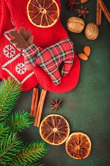 Christmas and new year's with fir branches, lighted candle, nuts and spices, and red socks with a toy deer fabric. top view