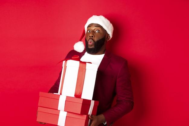 Natale, capodanno e concetto di shopping. felice uomo di colore con cappello da babbo natale e blazer in possesso di regali di natale, porta regali e sorride, in piedi su sfondo rosso