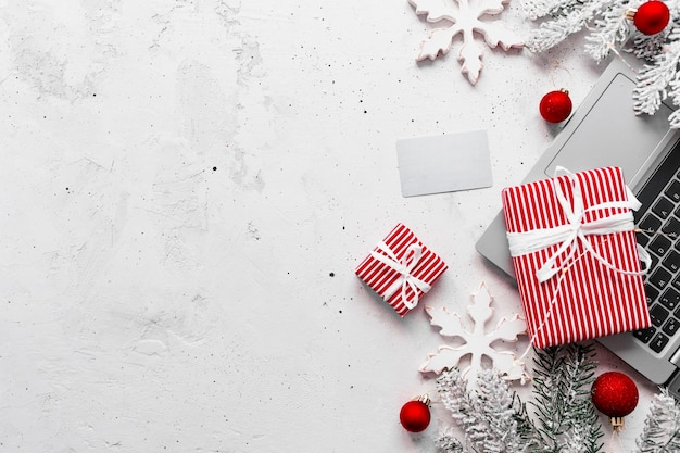 크리스마스, 새해 쇼핑 회색 콘크리트 플랫이 놓여 있습니다. 노트북 컴퓨터, 빈 신용 카드, 빨간색 흰색 종이 선물 상자 위쪽 전망. 전나무 가지, 장난감 공, 별. 사진에 공간 영역 복사