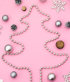 Christmas and new year. silhouette of a christmas tree made of beads with christmas toys and cones on a pink background. flat lay. copy space