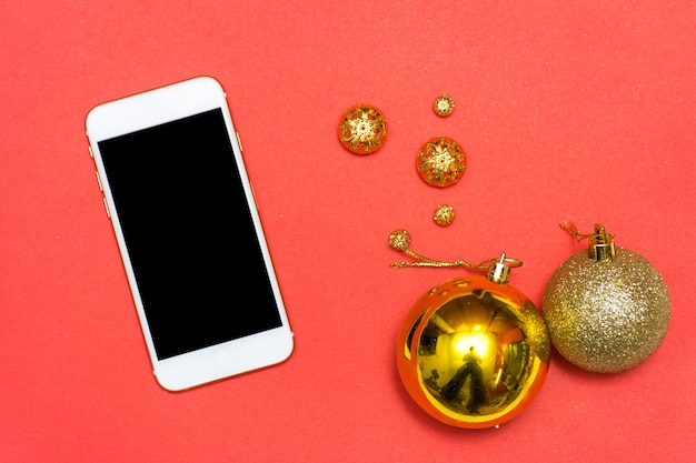 Christmas or new year smartphone background: fir tree branches, gold glass balls, decoration and cones on a red background