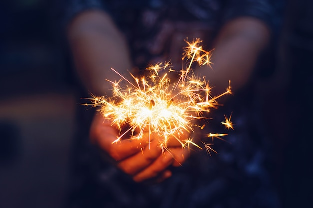 Christmas, new year sparkler in woman hands.