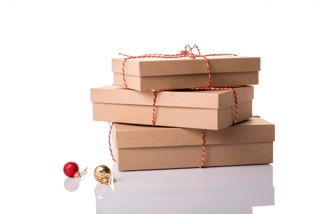 Christmas, new year stacked gift boxes, parcel, present packed in eco-friendly paper tied with rope, with red and golden baubles with shadow isolated