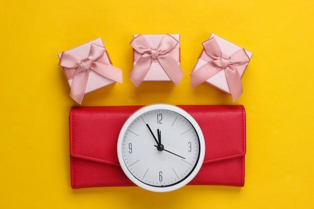 クリスマス、新年のテーマ。時計付きギフトボックス、黄色い表面に財布。上面図