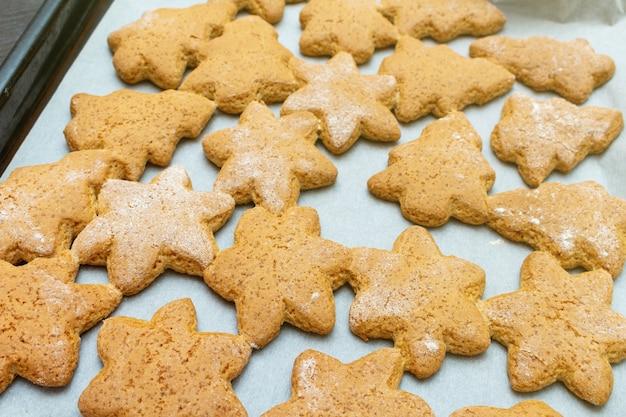 Рождество новый год традиционные домашние звезды и печенье в форме ели, процесс приготовления печенья