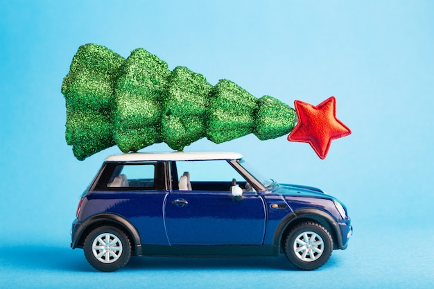 Christmas new year tree with red star on top of blue car toy roof. blue color background. creative miniature xmas tree on car.