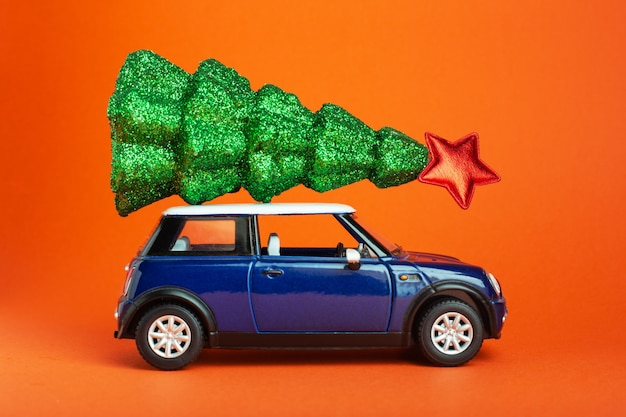 Christmas new year tree with red star on top of blue car toy roof. orange background. creative miniature xmas tree on car.