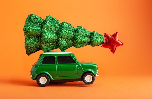 Christmas new year tree with red star on top of green car toy roof orange background creative