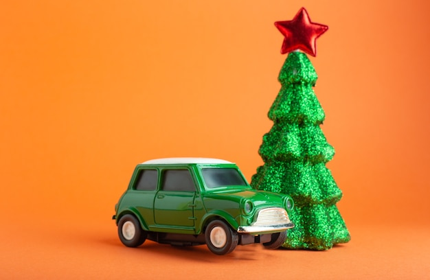 Christmas new year tree with red star on top near green car toy . orange background. creative miniature xmas tree and car. gift delivery concept.