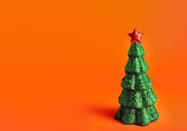 Christmas new year tree with red star on top. orange background with copyspace creative miniature glitter sequins xmas tree.