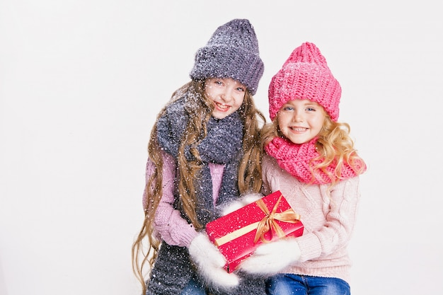 Christmas. new year. two little sisters holding present in winter clothes.pink, grey hats
