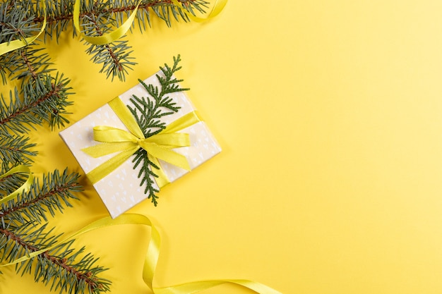 Рождество, новый год, день святого валентина ярко-желтый фон с подарочной коробкой diy и зелеными еловыми ветками, украшенными желтой лентой. вид сверху. горизонтальная ориентация. скопируйте место для текста.