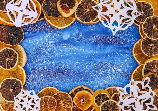 クリスマス、正月、冬の休日の構成。白い紙の雪片と、青い熟成した木の板に乾燥したオレンジのスライスがあります。お祭りフレーム。
