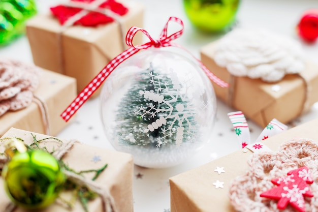 Christmas and new year with presents, decorations and transparent decorative ball with fir tree inside.