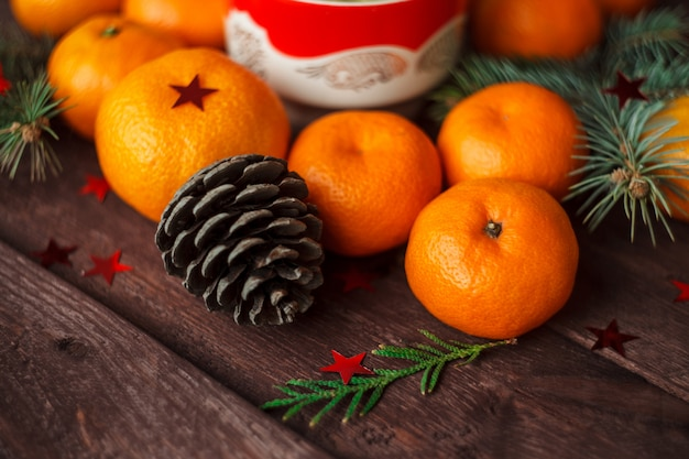 Christmas new year with tangerines, tea and sweets on the table. winter still. selective focus.