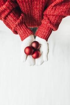 Рождество новый год рождественская композиция. молодая женщина в красном вязаном свитере и белых варежках держит елку красные елочные игрушки