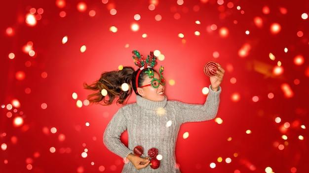 크리스마스 새해. 젊은 여자 손질 빨간 벽에 휴일에 크리스마스 장식품과 소품 공 빨간색 따뜻한 스웨터를 입고. 개념 메리 크리스마스.