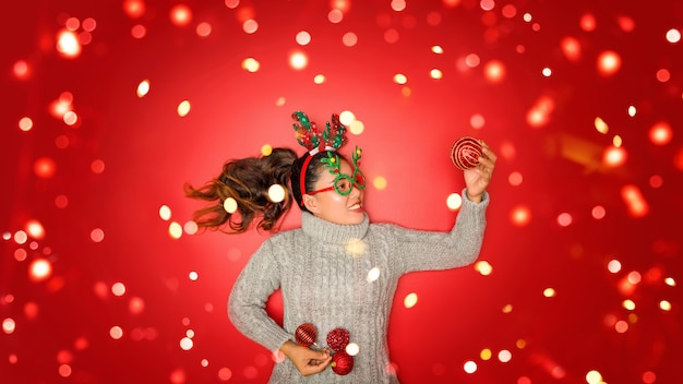 Christmas new year. young woman dressed in warm sweater with  props ball red with christmas ornaments in holiday on shine red wall. concept merry christmas.