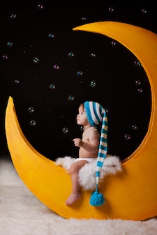Christmas night. babe, the boy sits on a yellow moon in  hat.