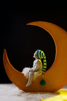 Christmas night. babe, the boy sits on a yellow moon in pajamas and a hat.