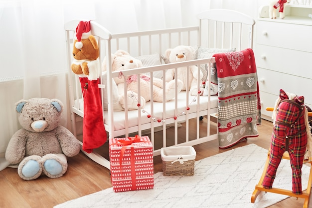 Christmas nursery, christmas decor in children's bedroom, children's playroom decorated for new year, white children's bedroom. christmas toys and gifts in children's bedroom, white bed with soft toys