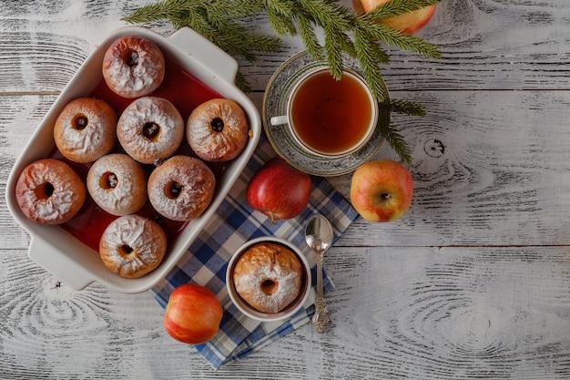 Рождество домашней печеных печеных яблок, специй, орехов, минусов и украшений на деревянном столе с копией пространства