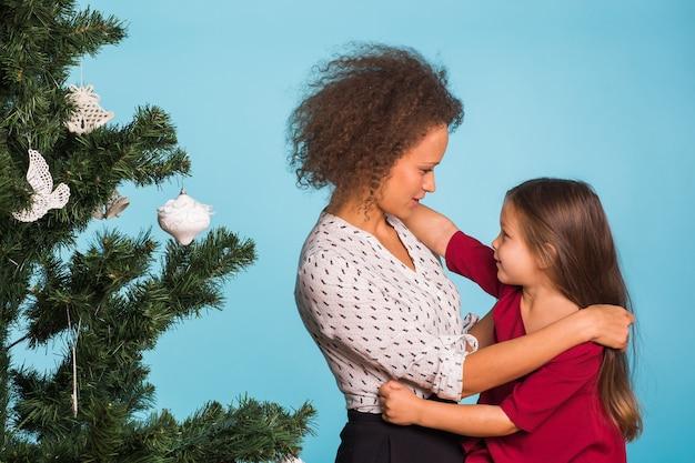 青いスペースにクリスマスツリーを持つ若いお母さんと娘のクリスマス。