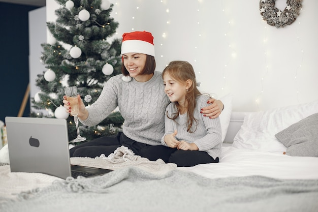 Рождество онлайн. празднование рождества нового года в карантине из-за коронавируса. вечеринка онлайн. мать с дочерью.