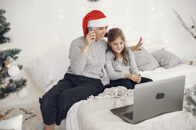 Natale in linea. celebrazione x-mas capodanno in quarantena coronavirus bloccata. festa online. madre con figlia.