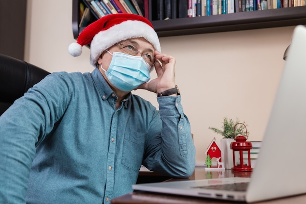 Christmas online congratulation idea. senior man in santa claus hat talks using laptop for video call friends and childrens. the room is festively decorated. christmas during coronavirus.