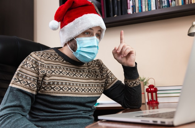 Christmas online congratulation idea. young man in santa claus hat and face mask talks using laptop for video call friends and childrens. christmas during coronavirus.