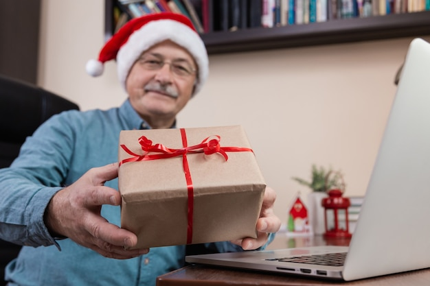Christmas online congratulation. senior man in santa claus hat gives a gift and talks using laptop device for video call friends and childrens. christmas during coronavirus.